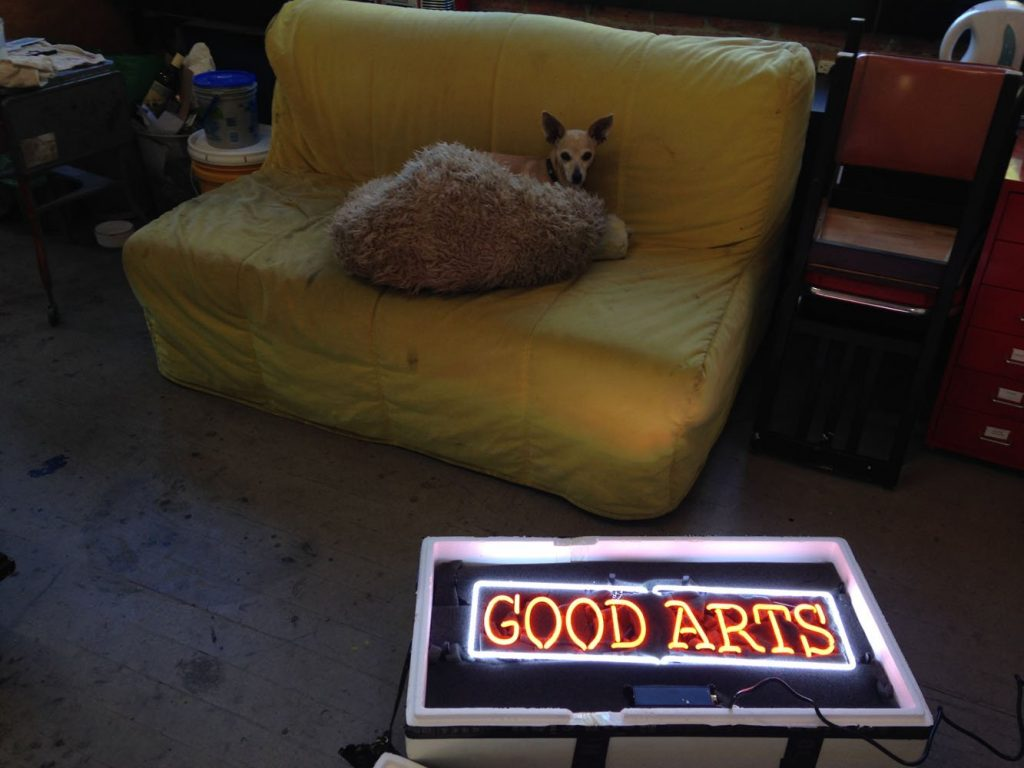 Good Arts sign guarded by attack chihuahua while awaiting installation